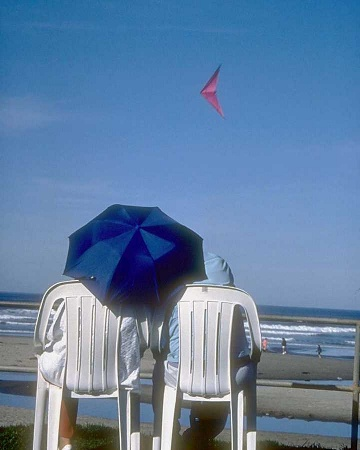A couple sitting in beach chairs on the beach